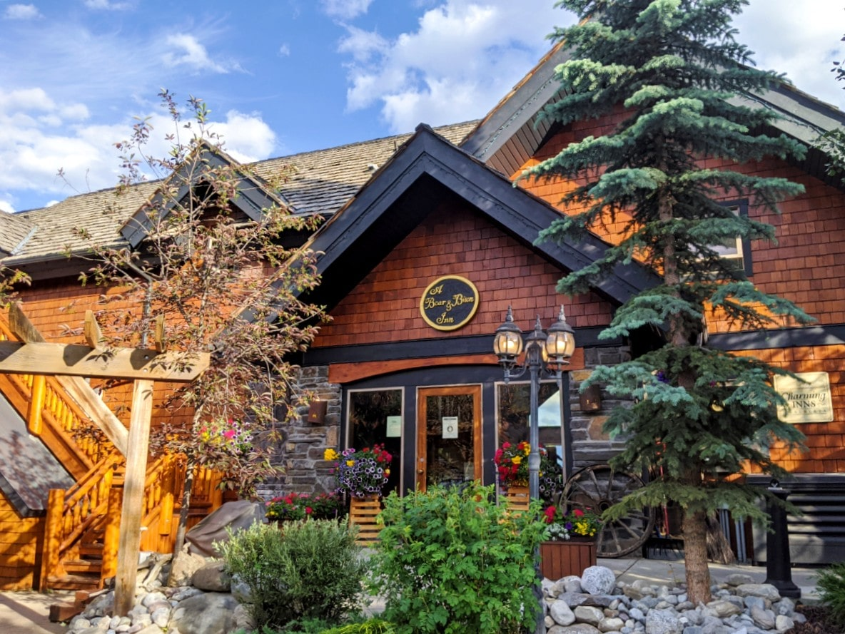 Entrance of Bear and Bison Inn with planted flowers, trees and wooden mountain chalet style