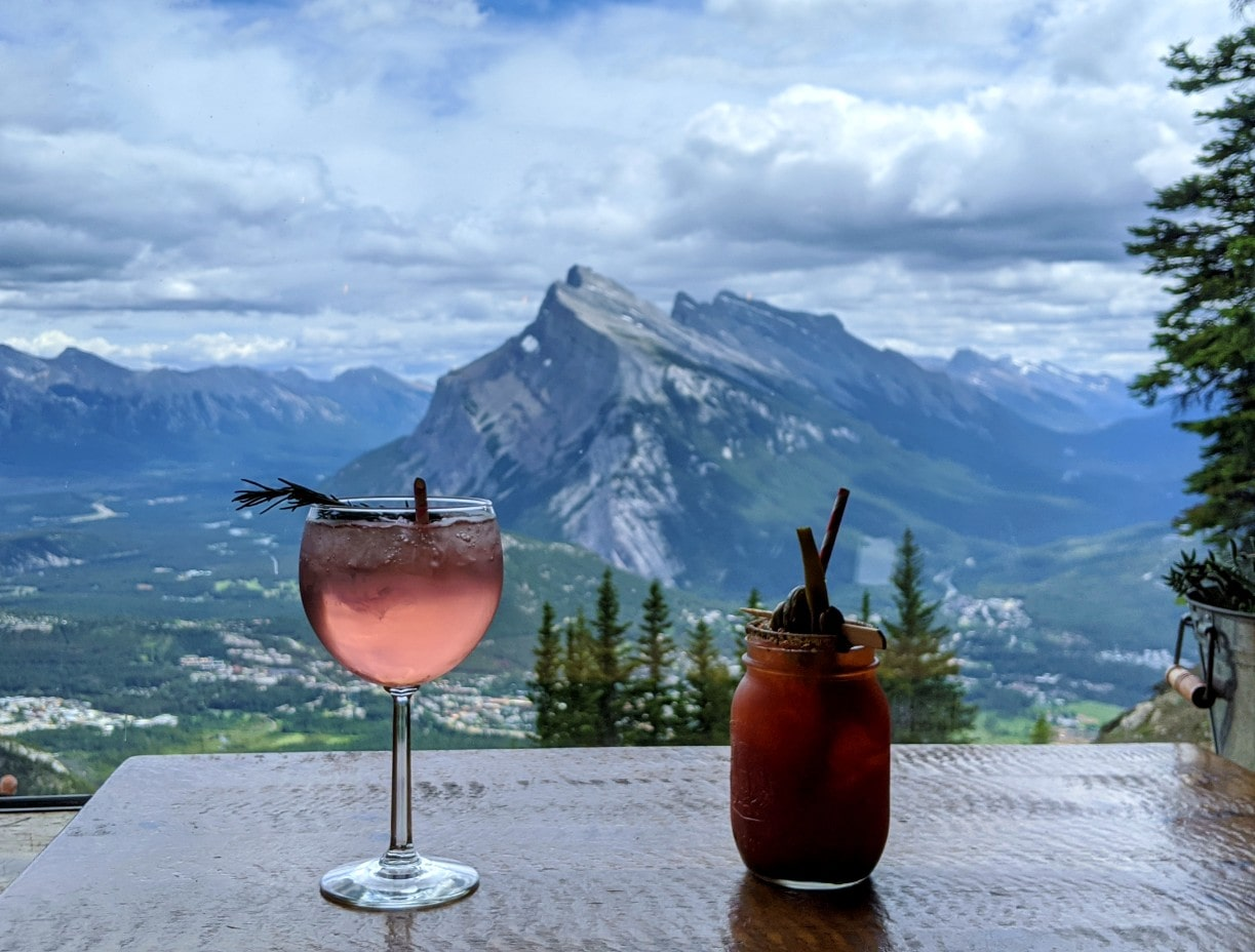 Two cocktails in front of bistro window with views of Mount Rundle behind