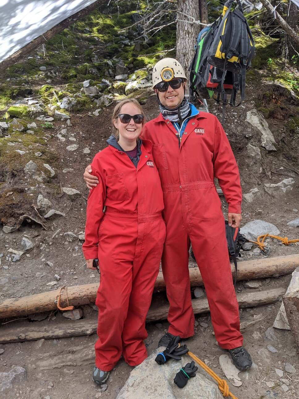 JR and Gemma standing together in red overalls smiling at camera, ready to start caving