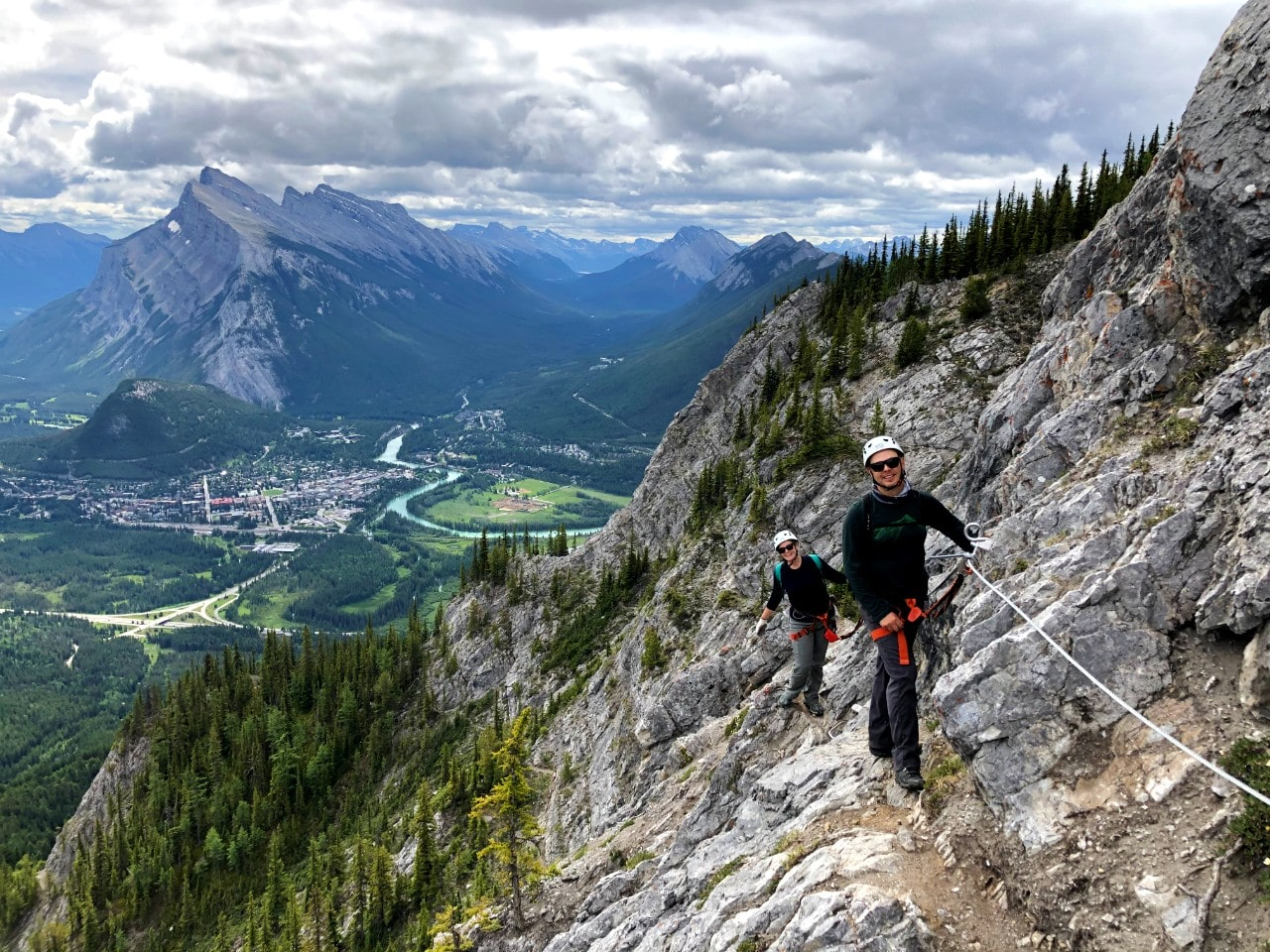 JR and Gemma on Via Ferrata course attached to rock with views of Banff and Mount Rundle behind