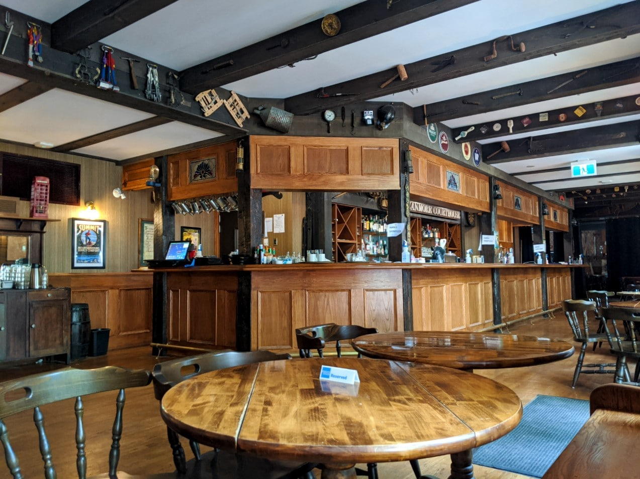 Inside the Miner's Lamp Pub, with English country pub style decor (wooden beams, wooden tables, paneled bar)