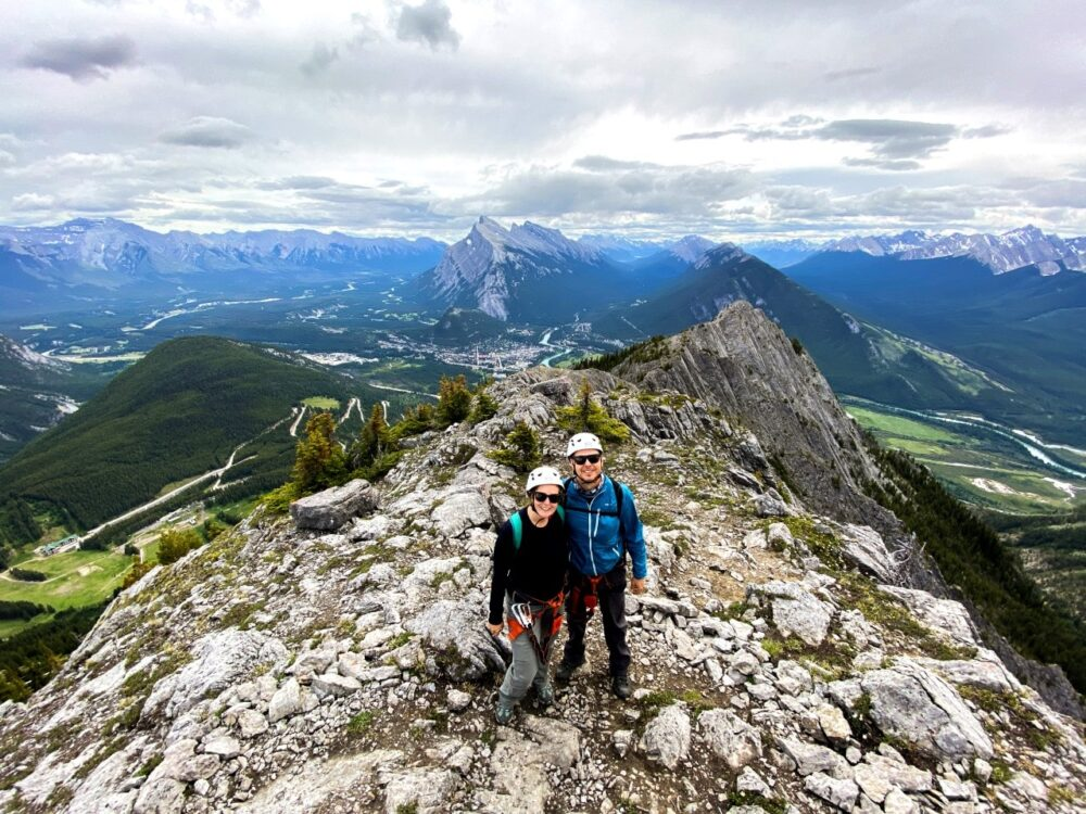 Gemma and JR standing together in front of the camera at the top of a mountain, with views of endless mountains and valleys behind