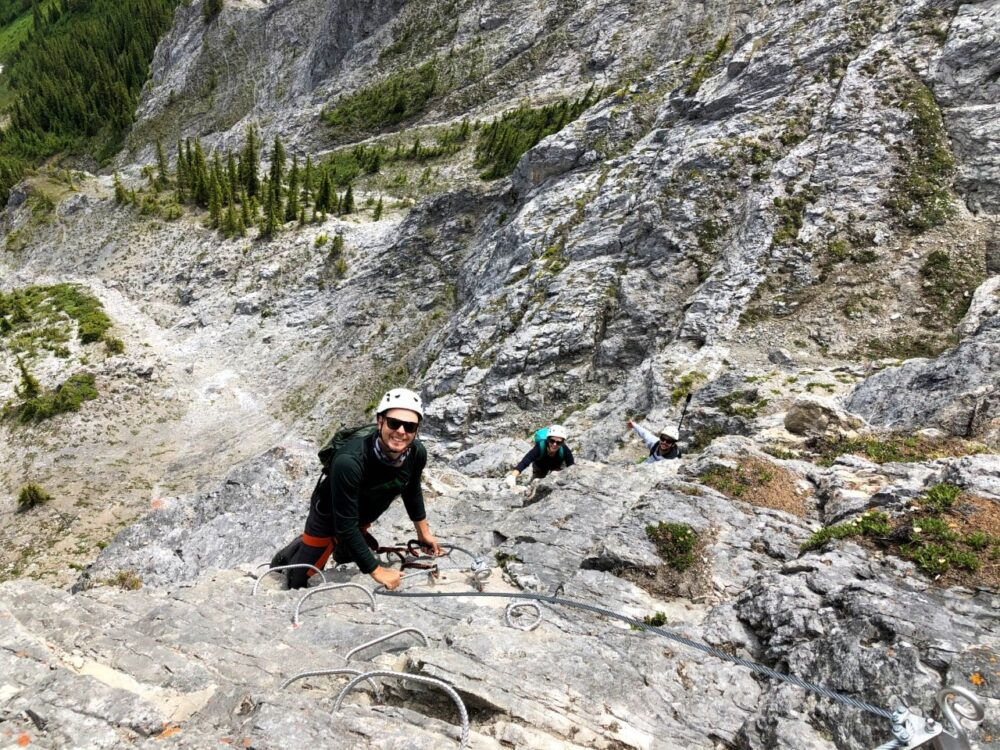Overhead view of Gemma and JR climbing up Via Ferrata course on rockface