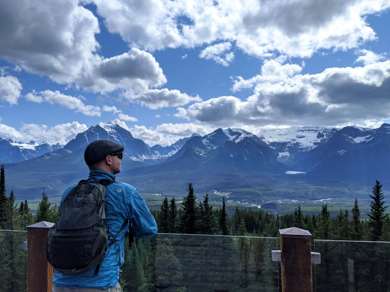 JR standing in front of glass patio fence at Lake Louise Ski Resort in front of mountainous views
