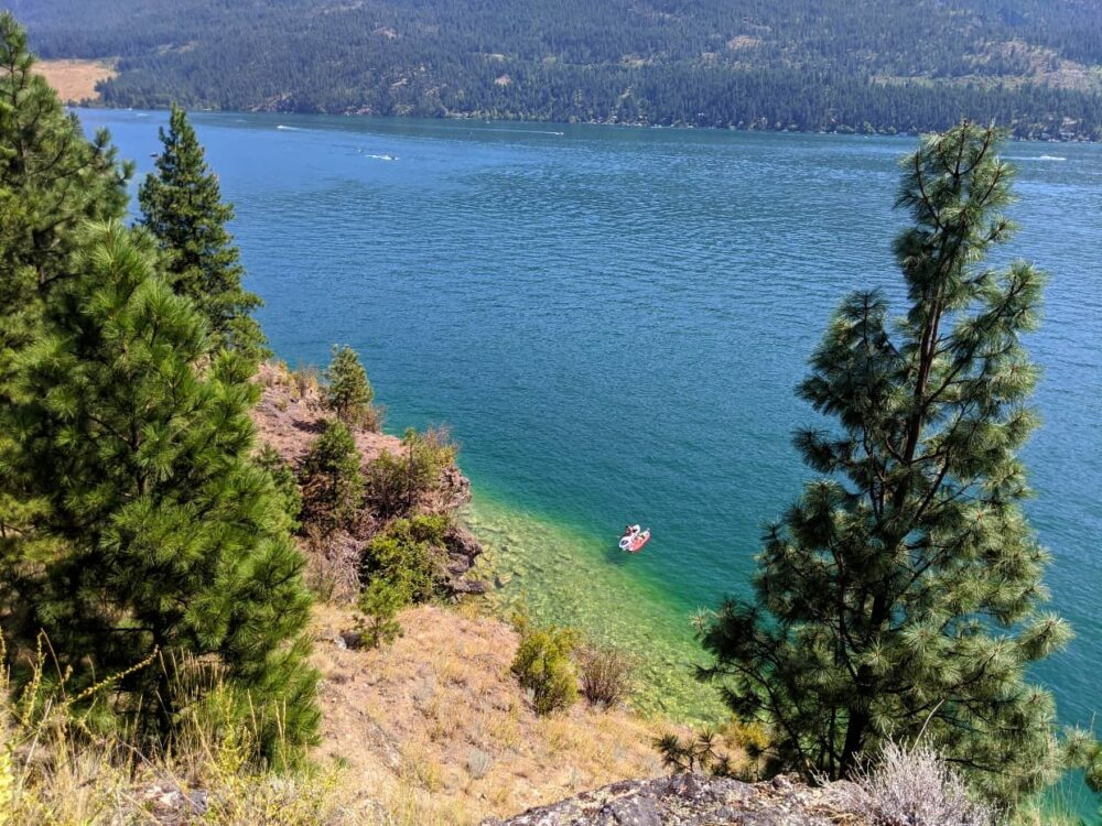 Looking down on two paddleboarders on Kalamalka Lake, with turquoise water underneath