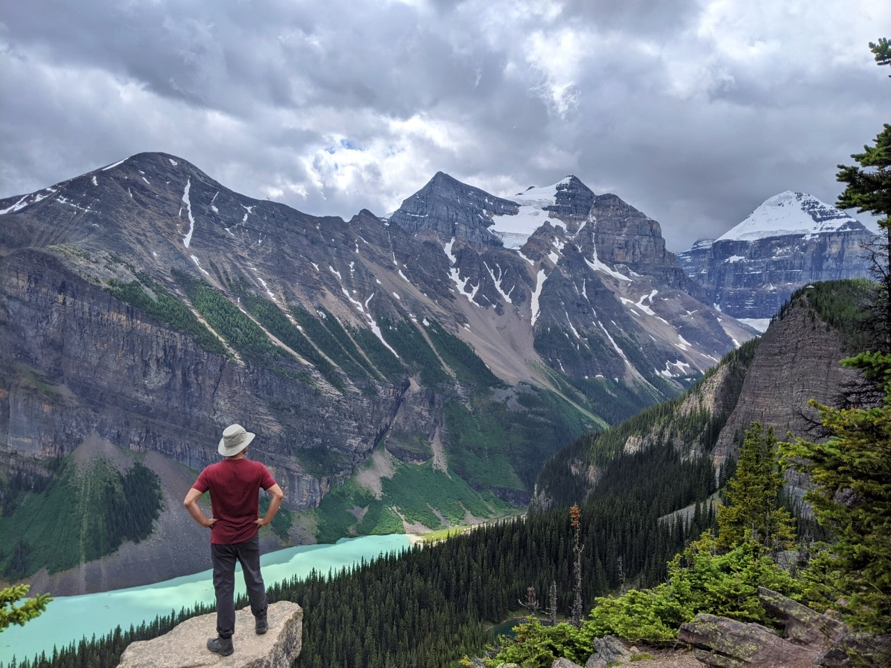 JR standing with back to camera looking down on bright Lake Louise, lined by snow capped mountains