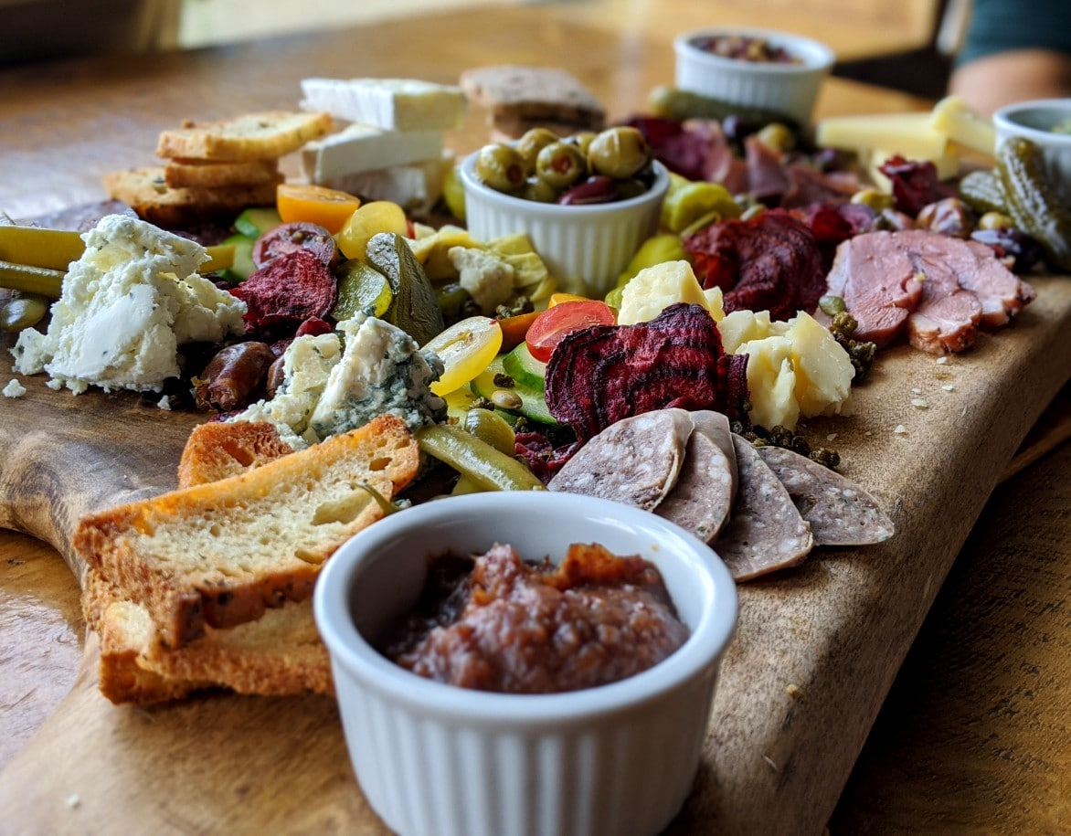 Wooden board covered with cheese, meat, vegetables, dips, bread and more at the Cliffhouse Bistro