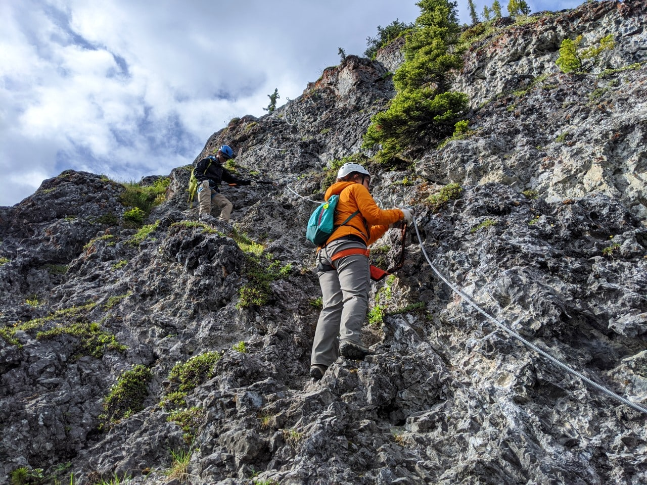Gemma standing on rock connected to steel safety cable on Mt Norquay Via Ferrata in Banff