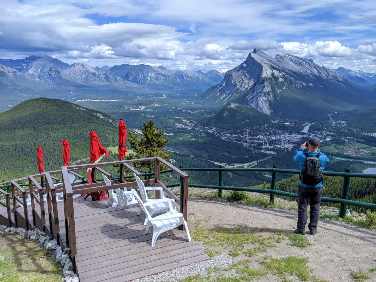 JR standing in front of mountain views at the top of Mt Norquay chairlift, taking a photo