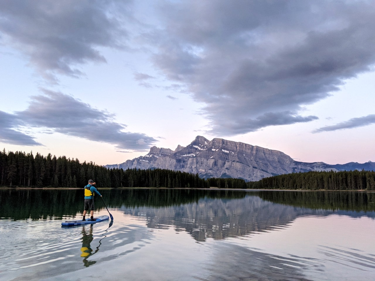 JR standing on paddleboard on calm Two Jack Lake near Banff with mountain background and sunrise colours