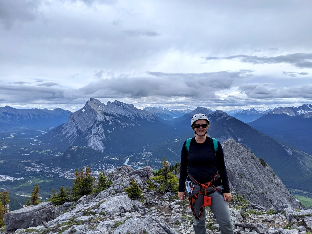 Gemma standing at the top of Mt Norquay Via Ferrata looking at camera with views of mountains and Banff behind
