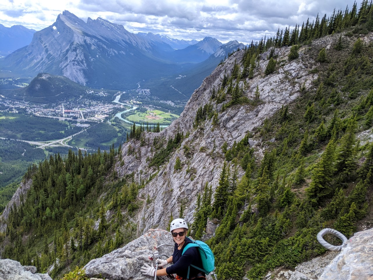 Gemma sat on rock looking at camera with elevated views behind of Banff, Mount Rundle and other mountains