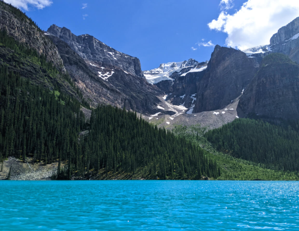 Canoe view of Emerald Lake with turquoise water, deep green forest and rugged mountains behind with glacier now visible