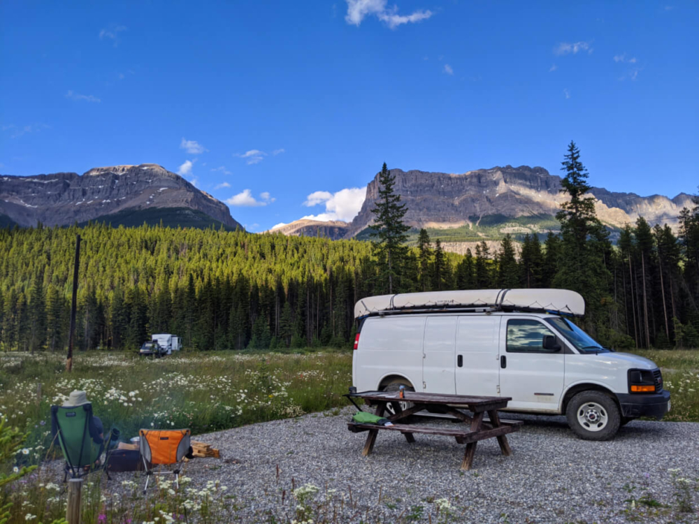 White van parked next to picnic table with mountainous background