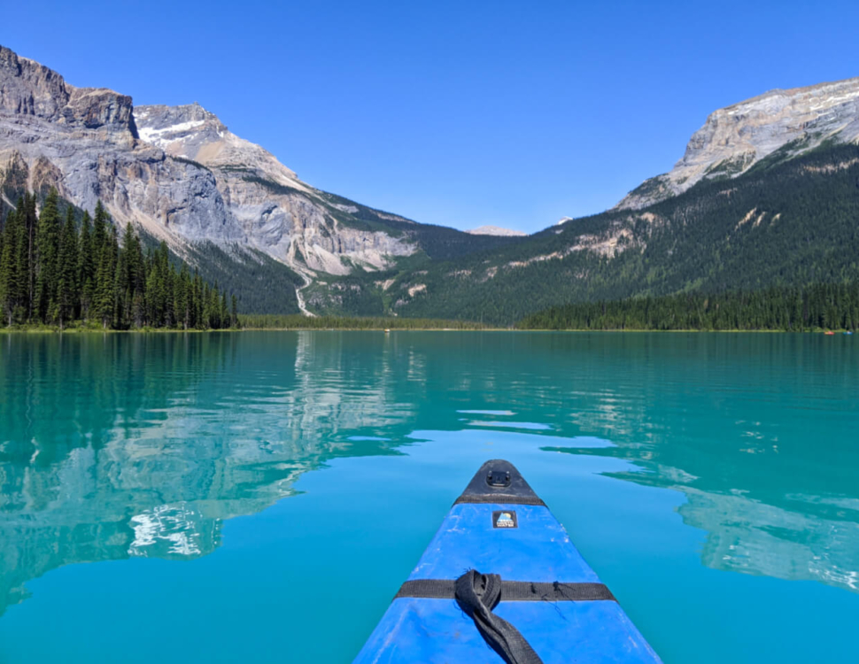 Canoeing Emerald Lake with turquoise coloured water with mountain reflections