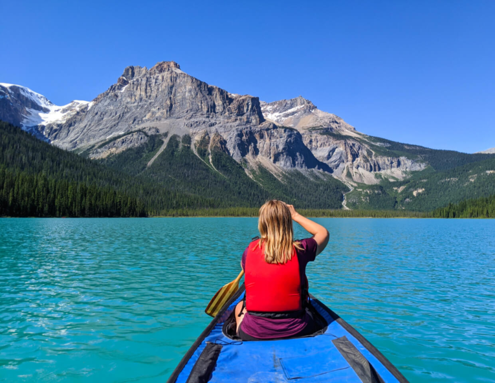 Back view of Gemma sat in canoe paddling on Emerald Lake, with bright turquoise water with mountainous backdrop
