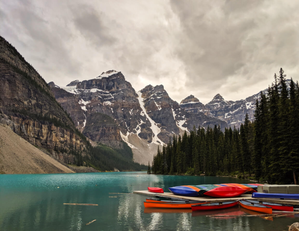 Rental dock on Moraine Lake with brightly coloured canoes in front of mountainous background