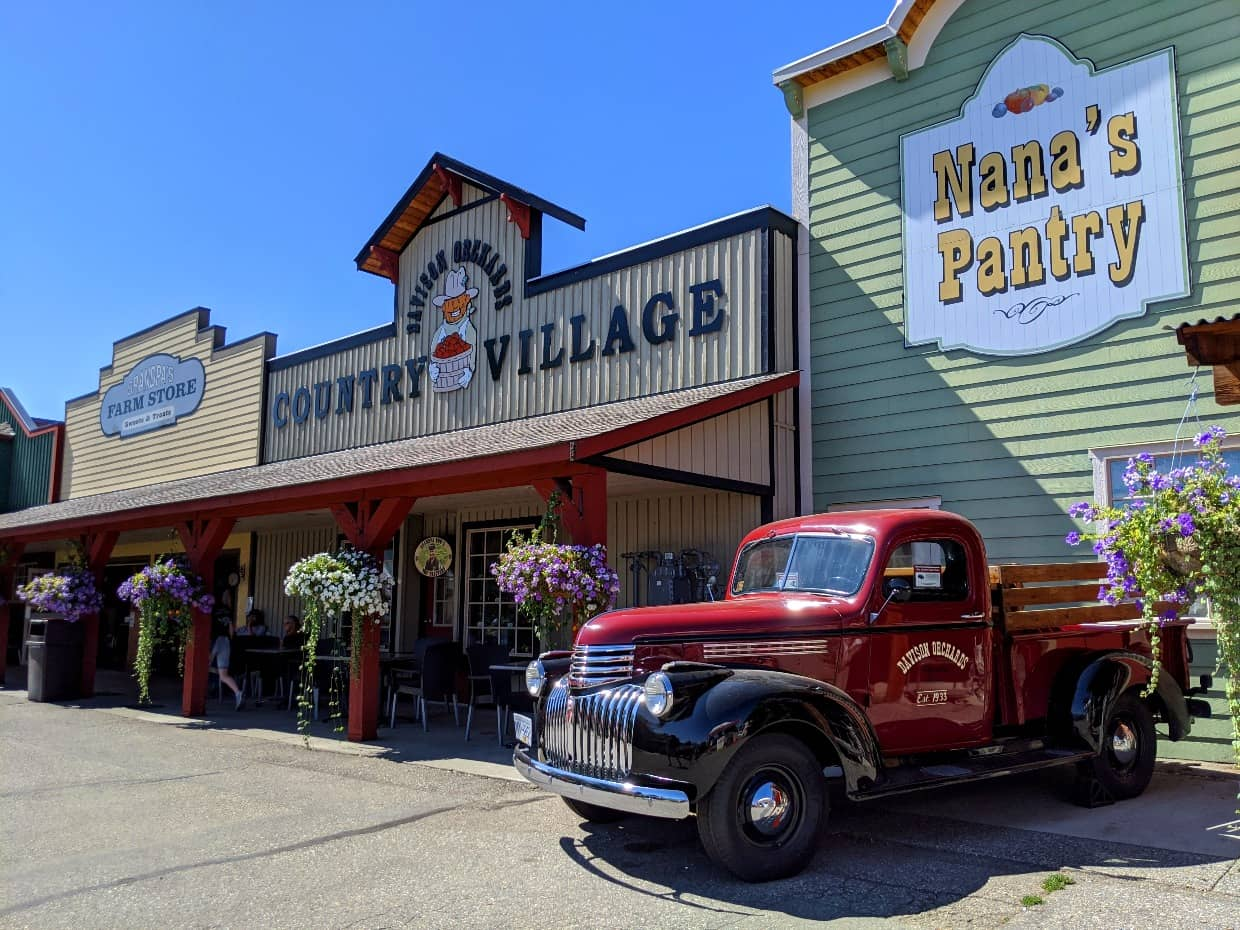 Old rec truck parked outside Davison Orchards country Village buildings with hanging flowers and wooden frontage