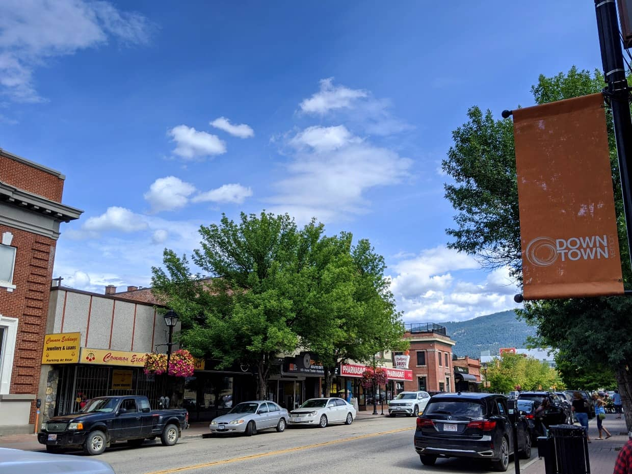 Street view of downtown Vernon with parked cars, shops, trees and orange downtown sign