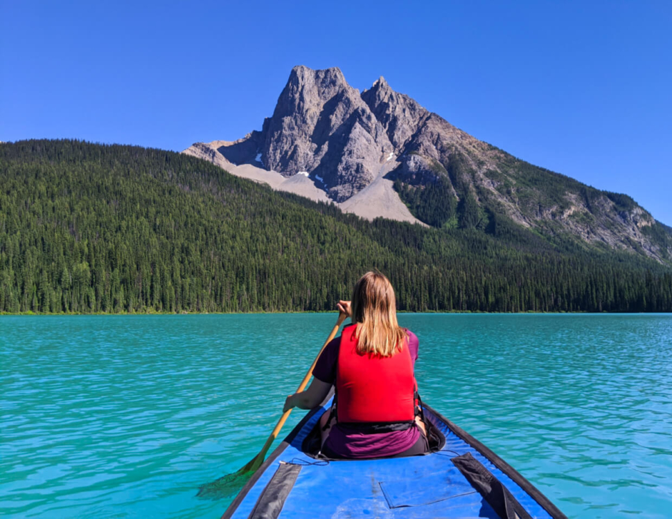 Canoe view with Gemma in front, paddling on Emerald Lake with impressive mountain formation behind