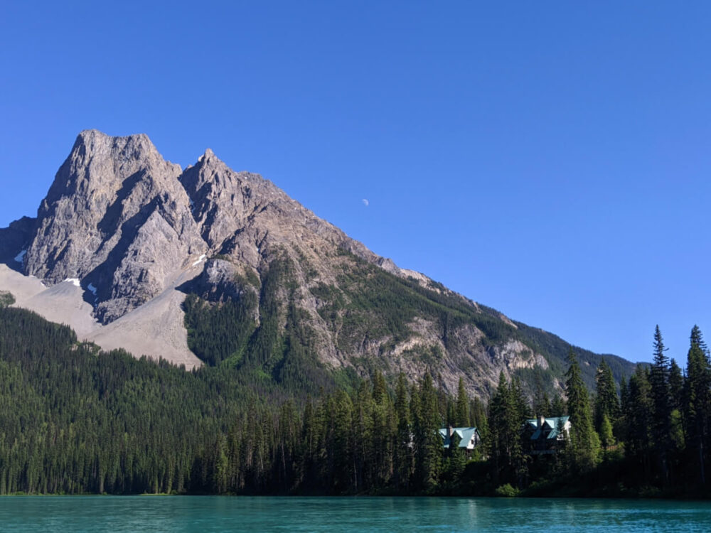 Two multi floor cabins set into forest on the shore of Emerald Lake with multi peak mountain behind