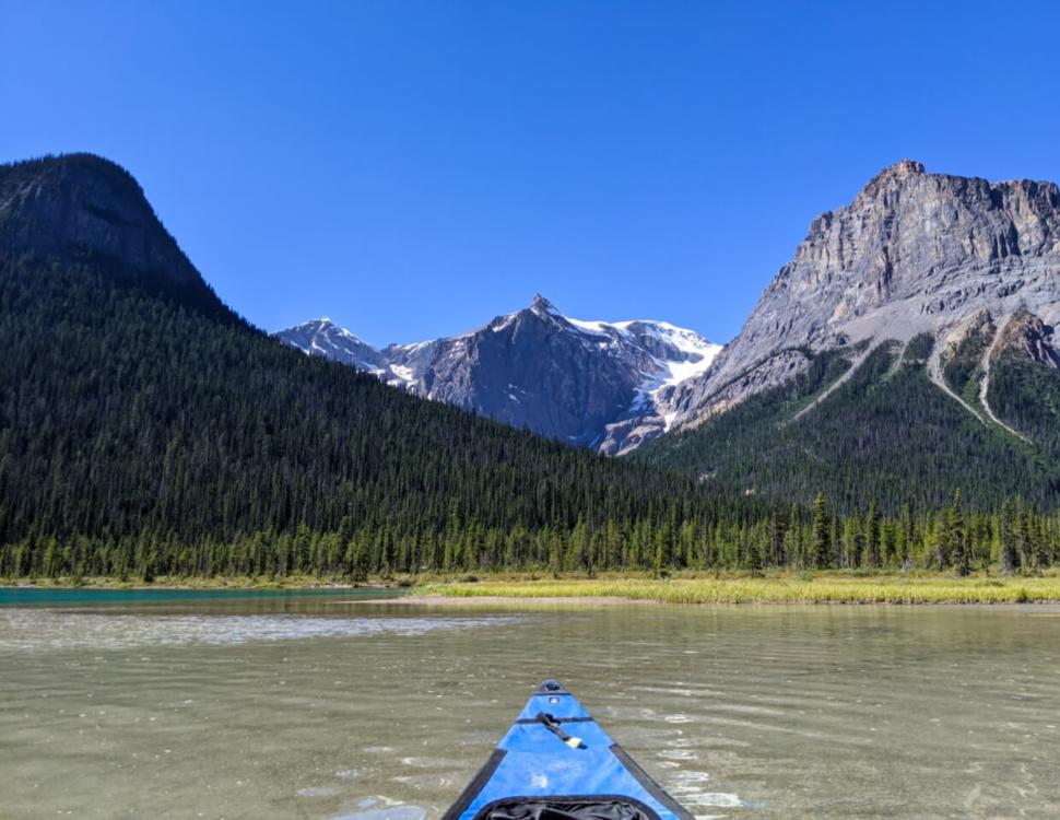 Canoeing Emerald Lake shoreline with trees lining lake and mountainous backdrop