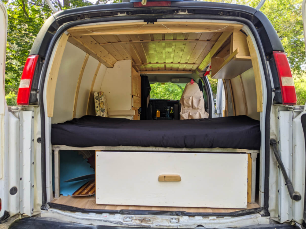 Back view of van with wooden ceiling, mattress on bed, white panel walls, large underbed drawer