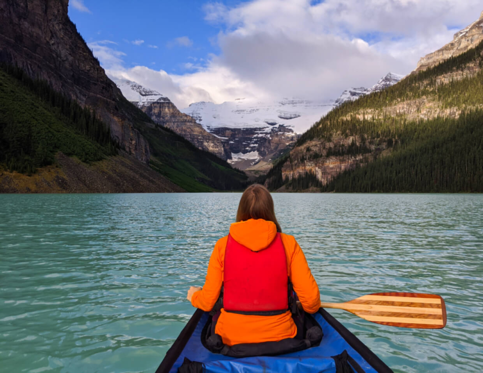Gemma sat in canoe with wooden paddle looking towards VIctoria Glacier on Lake Louise