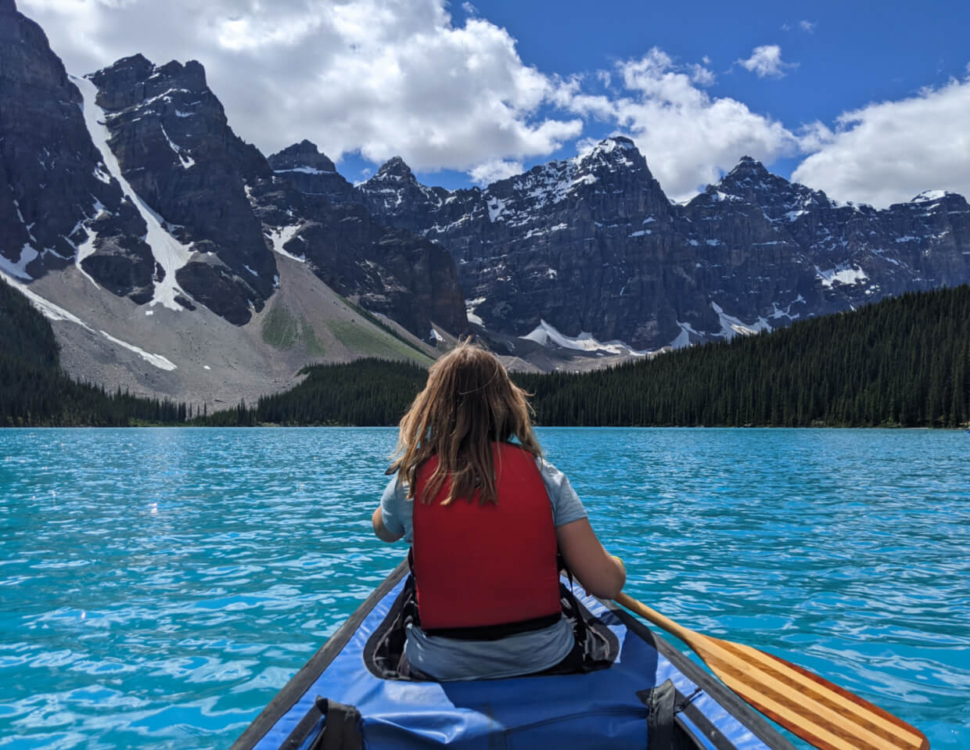 Gemma paddling canoe on Moraine Lake, with turquoise water and mountainous backdrop