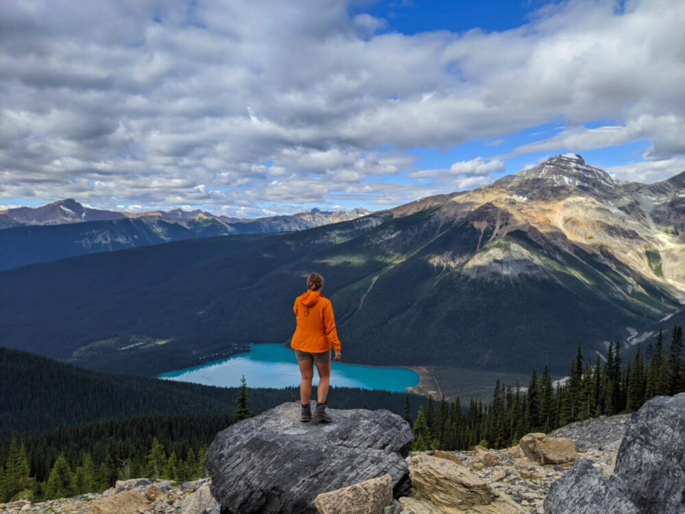 Gemma standing on rock in front of scenic view featuring brightly coloured Emerald Lake and surrounding mountains