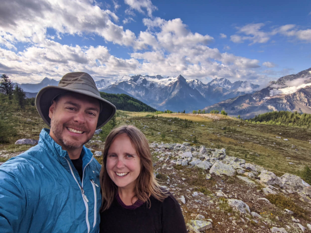 Gemma and JR selfie in front o meadow, surrounded by mountains and glaciers