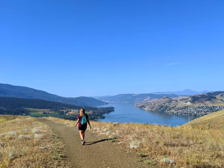 Gemma hiking away from camera on Vernon hiking trail on Middleton Mountain, with views of Kalamalka Lake behind