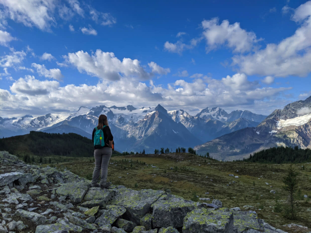 Gemma standing on rocky ridge in front of endless mountains and glaciers on the Monica Meadows Trail