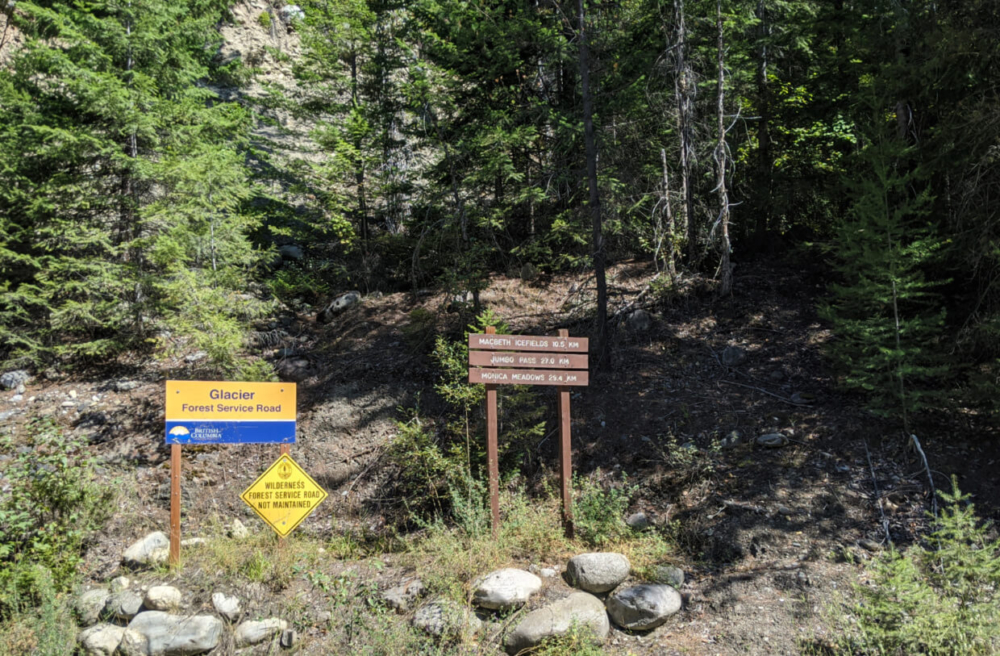 Wooden Forest Service Road signs noting distances to hiking trails