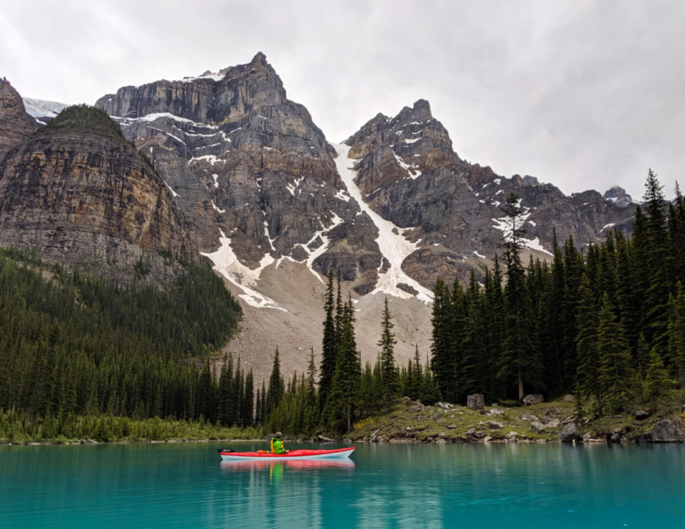 JR sat in red kayak on Moraine Lake, with mountainous background