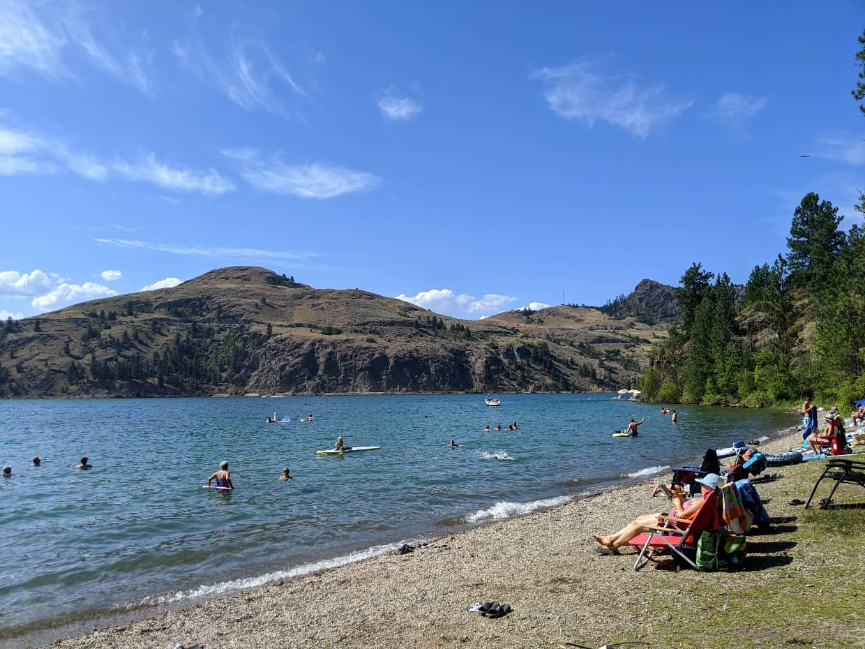 Lakeshore beach in Kalamalka Lake Provincial Park in Vernon, with people sunbathing on beach and swimmers in lake