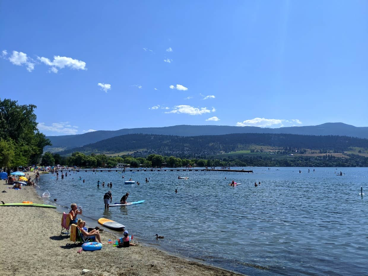 Lakeshore with people on beach and in the water, swimming and on stand up paddleboards