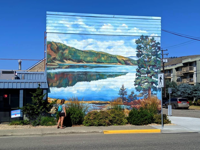 Gemma standing on sidewalk looking up at Kalamalka Lake mural in Vernon, BC