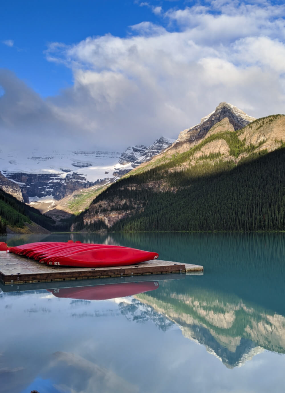 View of Lake Louise with mountain reflections and canoe dock