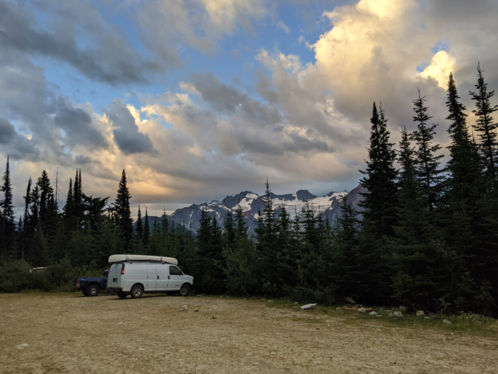 White van and blue truck parked in cleared area, lined by trees with mountains in background