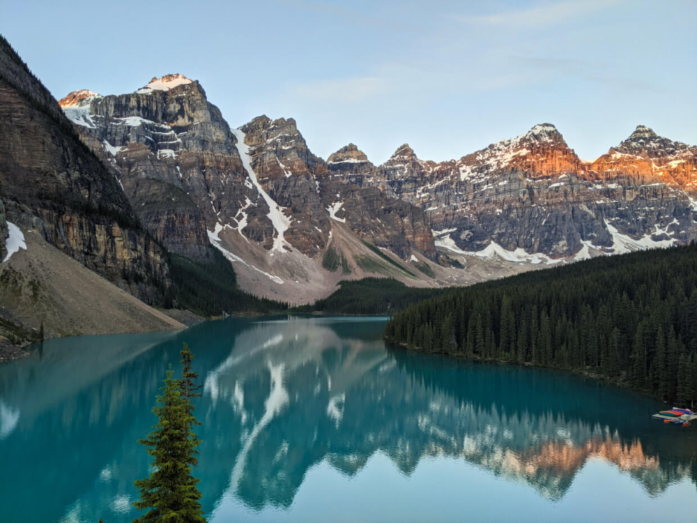 Elevated view of Moraine Lake with reflections of surrounding mountains in water, with canoe dock on right