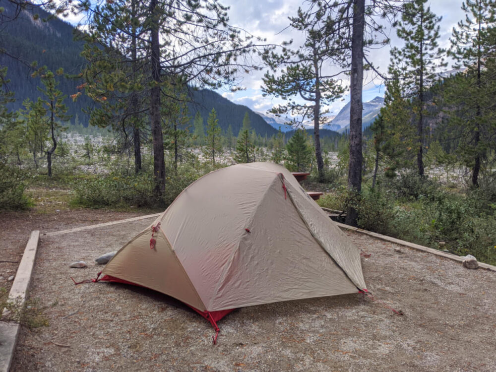 Set up tent on dirt tent pad in national park campground, with mountainous background
