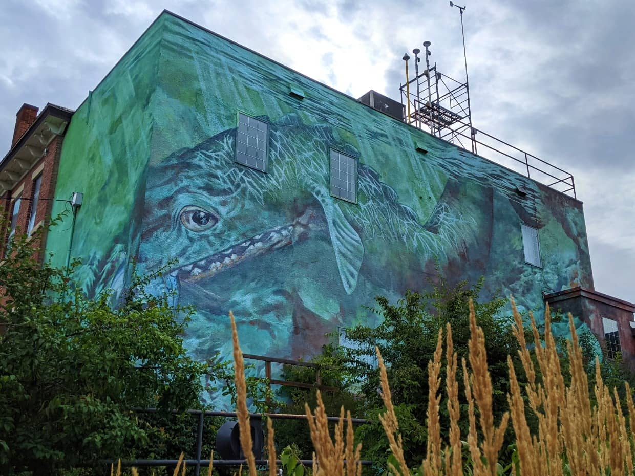 Brick wall of Okanagan Science Centre with painted green/blue Ogopogo monster mural