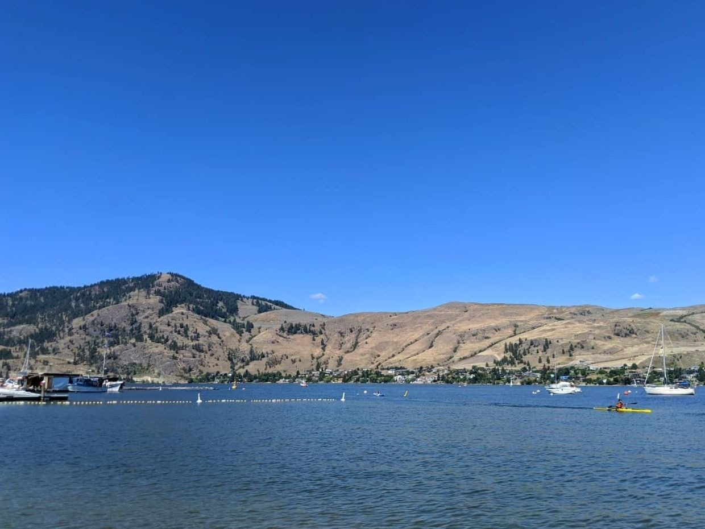Okanagan Lake view from Paddlewheel beach with kayaker and grassland hills behind