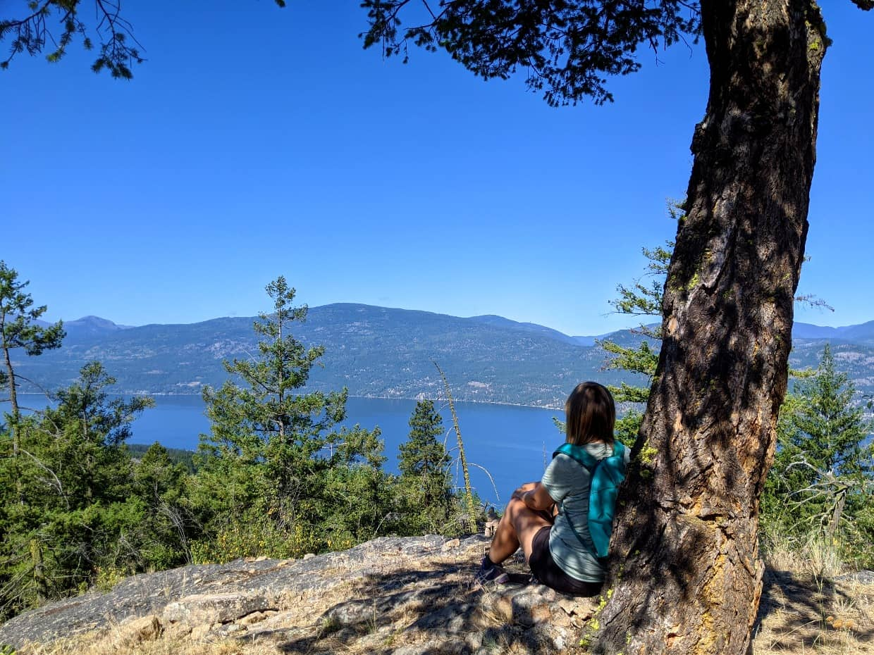 Gemma sat in front of shady tree with elevated view of Okanagan Lake