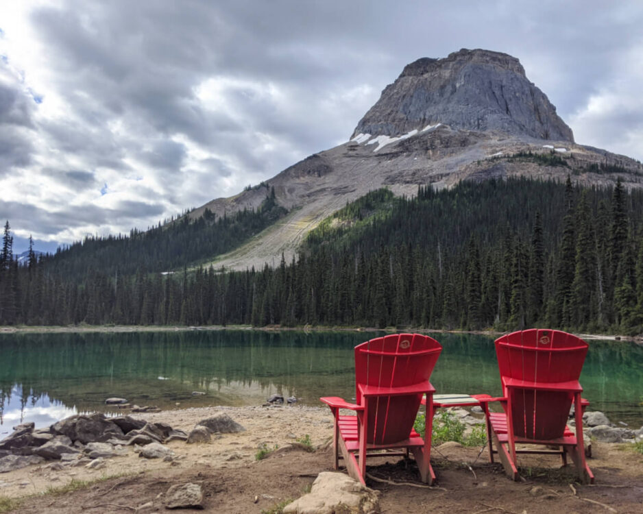 Two red Parks Canada chairs in front of turquoise coloured Yoho lake, which is backdropped by sloping Wapta mountain