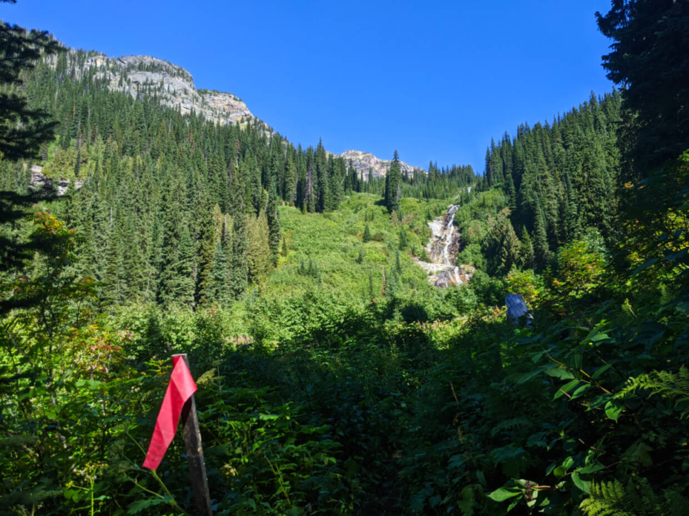 Red flag next to trail with waterfall and snow capped mountain behind