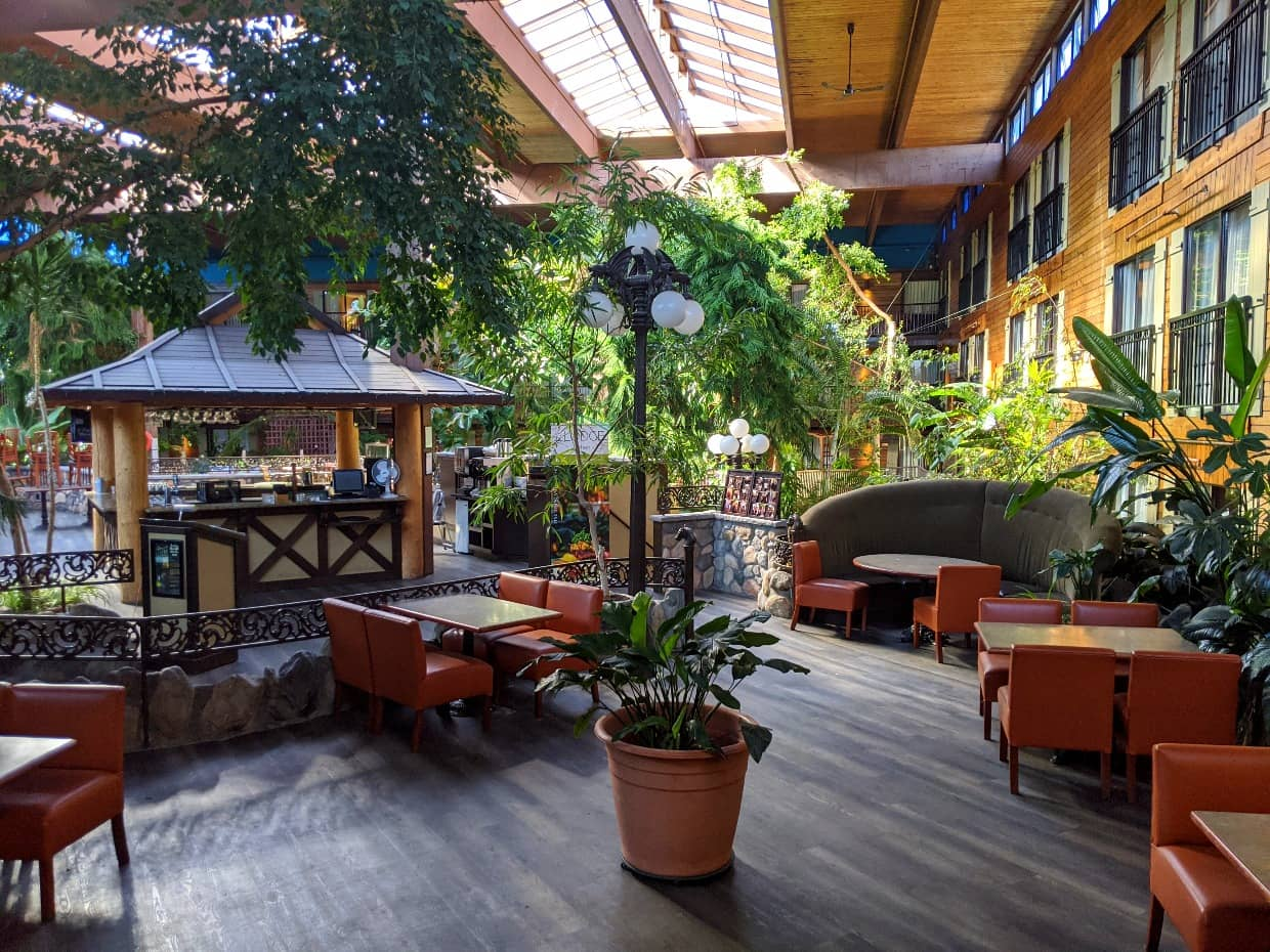 Restaurant with orange chairs and wooden flooring in glass atrium at Prestige Lodge hotel with tropical plants