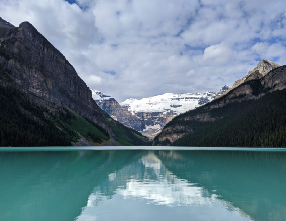 Shore view of Lake Louise with reflections of mountains and glacier behind