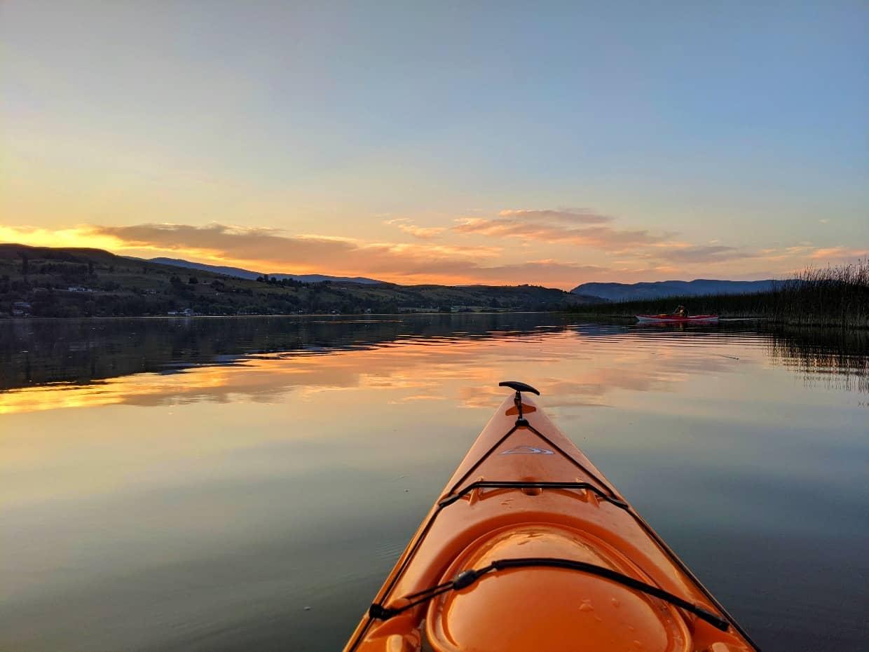 Kayak view of Swan Lake at sunset with orange yellow skies and calm water